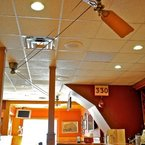 Brewmaster belt-driven ceiling fan, antique brass finish, with wooden cherry finish blades, in a bar