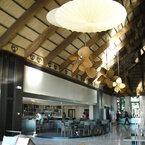 Palisade ventilador de techo de rotación vertical, latón antiguo, con aspas de hoja de palmera, en el lobby de un hotel