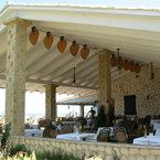 Punkah ventilador de techo / pared, negro, con aspas de bambú, en una terraza cerca del mar