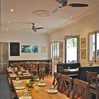 Soho ventilador de techo, níquel cepillado, con aspas de madera de color chocolate, en un restaurante mediterráneo